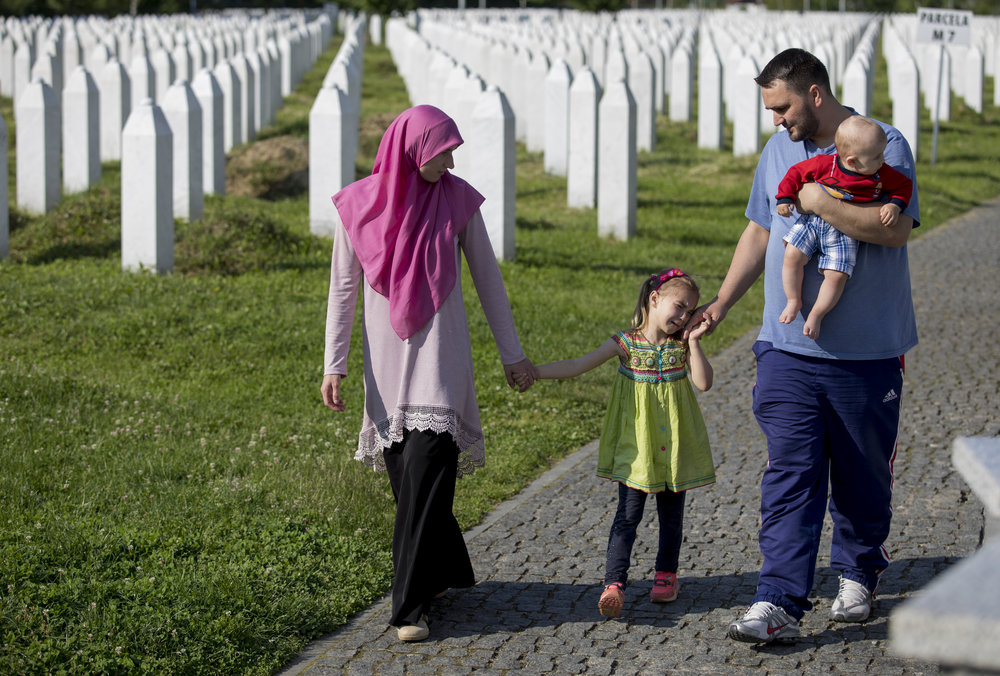 Almedina Mujkanovic, left, and her husband, Nermin, brought their daughter, Nahla, 5, and son, Harun, 1, to the Srebrenica Genocide Memorial to remember the family's loved ones who were among the over 7,000 Bozniak Muslims killed in the massacre of July 1995. The memorial stands as a reminder of the atrocities committed during the Bosnian War.