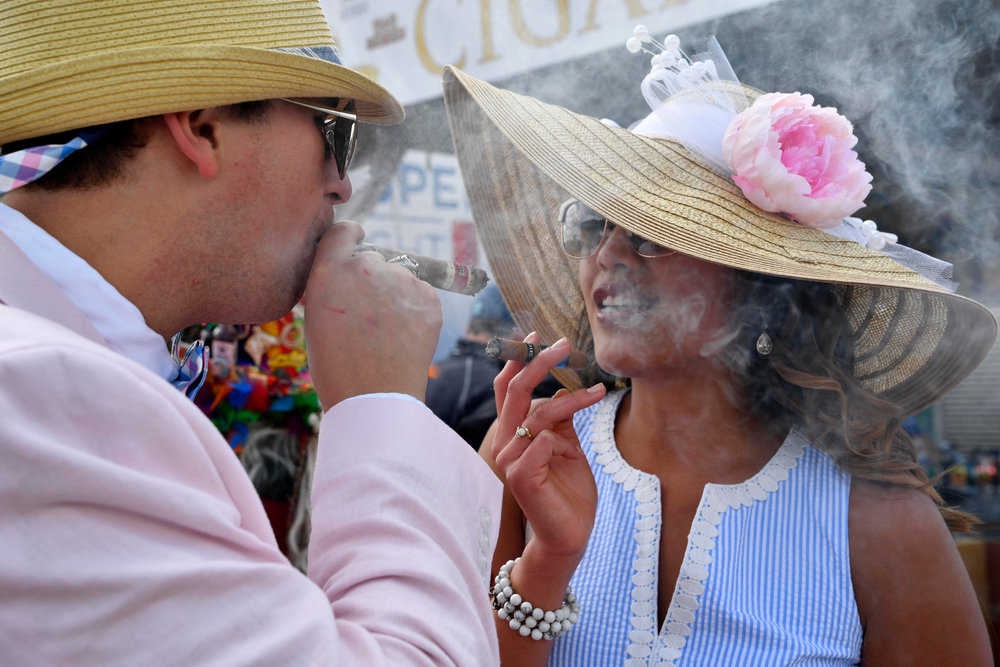 May 6, 2017; Louisville , KY, USA; John Sell and Megan Mejia smoke cigars in their derby hats on the infield before the 2017 Kentucky Derby at Churchill Downs.