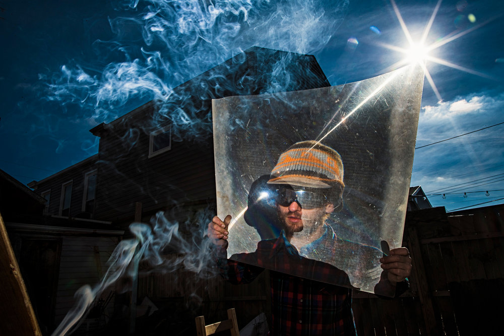 "Solar artist, Billy Keith, uses a large magnifying glass to burn art work into a piece of scrapped wood in the backyard of his home in Louisville, Kentucky. Keith began collecting lenses in 2008. ""I started doodling in 2009 and after a near death experience in 2010, I started taking it a lot more serious."" Keith can often be found creating art along the sidewalks of Fourth Street during the sun's peak hours between 11 am and 2 pm. ""I had a regular job for years. I was the bread man for 11 years,"" Keith said. ""I don't want to get a regular job again, but sometimes it's hard to get motivated. If you're ever going to do anything, you just got to get out and do it."" Keith's home is full of scrapped wood that he has burned art, ranging from landscapes to figures, and he hopes some day he will be discovered for his talent. Nov. 22, 2017"