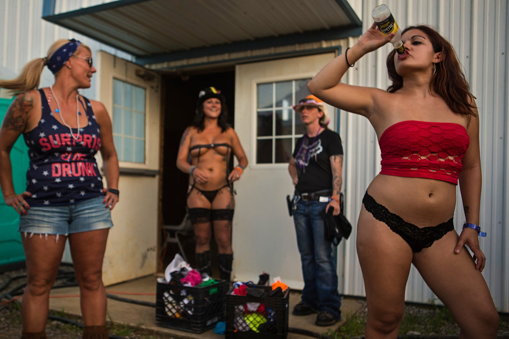 "Miss Sturgis contestant Victoria Alcisto, right, chugs a bottle of Mike's Hard Lemonade before the start of the 2017 Miss Sturgis pageant at the Sturgis Kentucky Bike Rally. ""This is my frist time at this rally,"" Alcisto said. The vagabond had met some friends at one rally and decided to tag along to check out the Sturgis, Ky event. Each July, nearly 20,000 descend upon the small Kentucky town of Sturgis, population 1,890. Kentucky's largest biker rally began in 1993 and was originally coined ""Little Sturgis,"" a reference to the largest bike rally in the nation, Sturgis, South Dakota. ""It's a family reunion of sorts. A lot of people come to make new friends and for new bonds and just have the experience,"" rally spokesperson Doug Rodgers said. ""It's an escape from reality."" July 14, 2017"