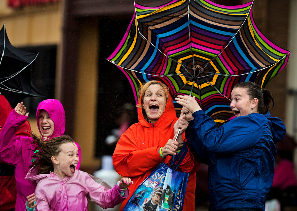 Roe Squire, left, and Annie Southworth try to wrangle in their umbrella after a gust of wind came down Broadway during the KDF Pegasus Parade on Thursday, May 4, 2017.