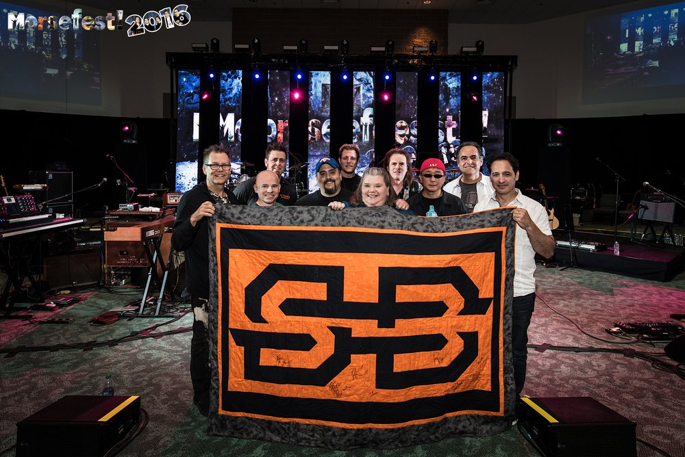 My Husband and I with the musicians of Spock's Beard at Morsefest 2016.  I designed and made this quilt for my husband with the band's logo, then had everyone in the band sign it.  Combining my love of music AND quilting.  Geek, right?