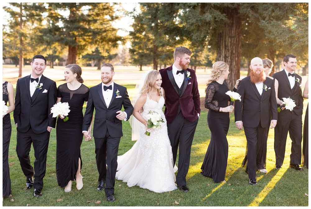 bride and groom laughing together with their bridal party for a New Years Eve wedding