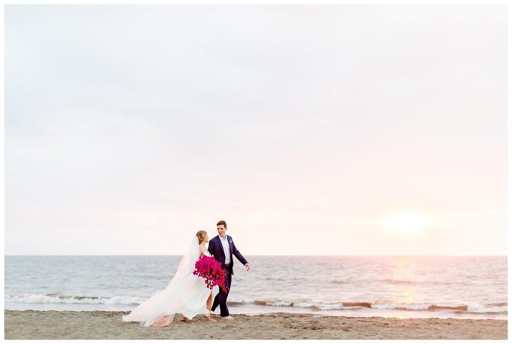 destination wedding photographer takes their couple on the beach for their sunset portraits