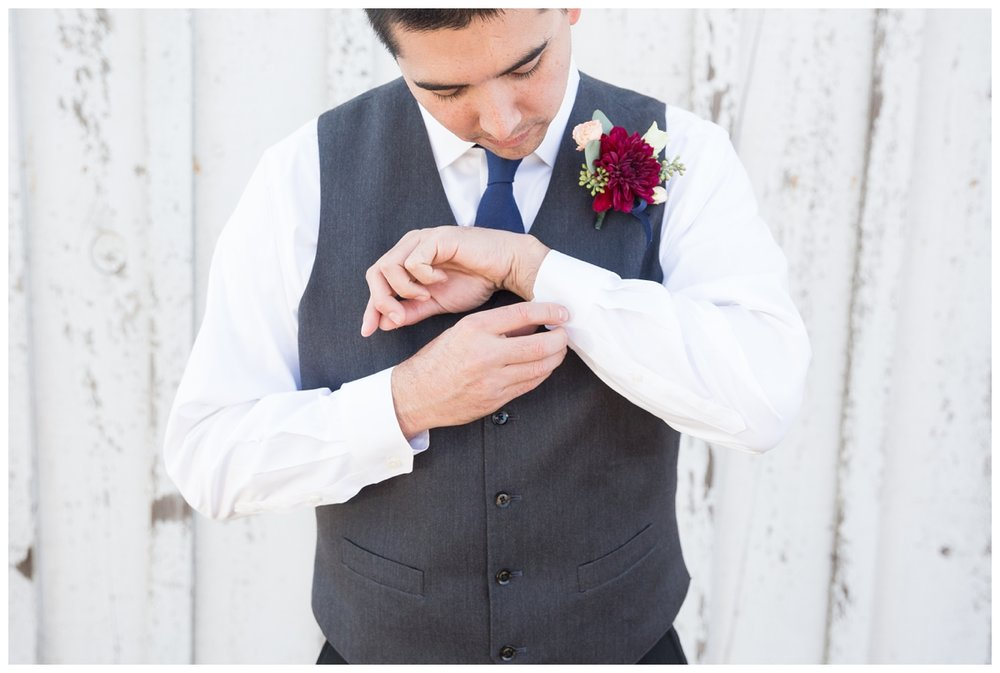 groom adjusting his boutinear on his wedding day