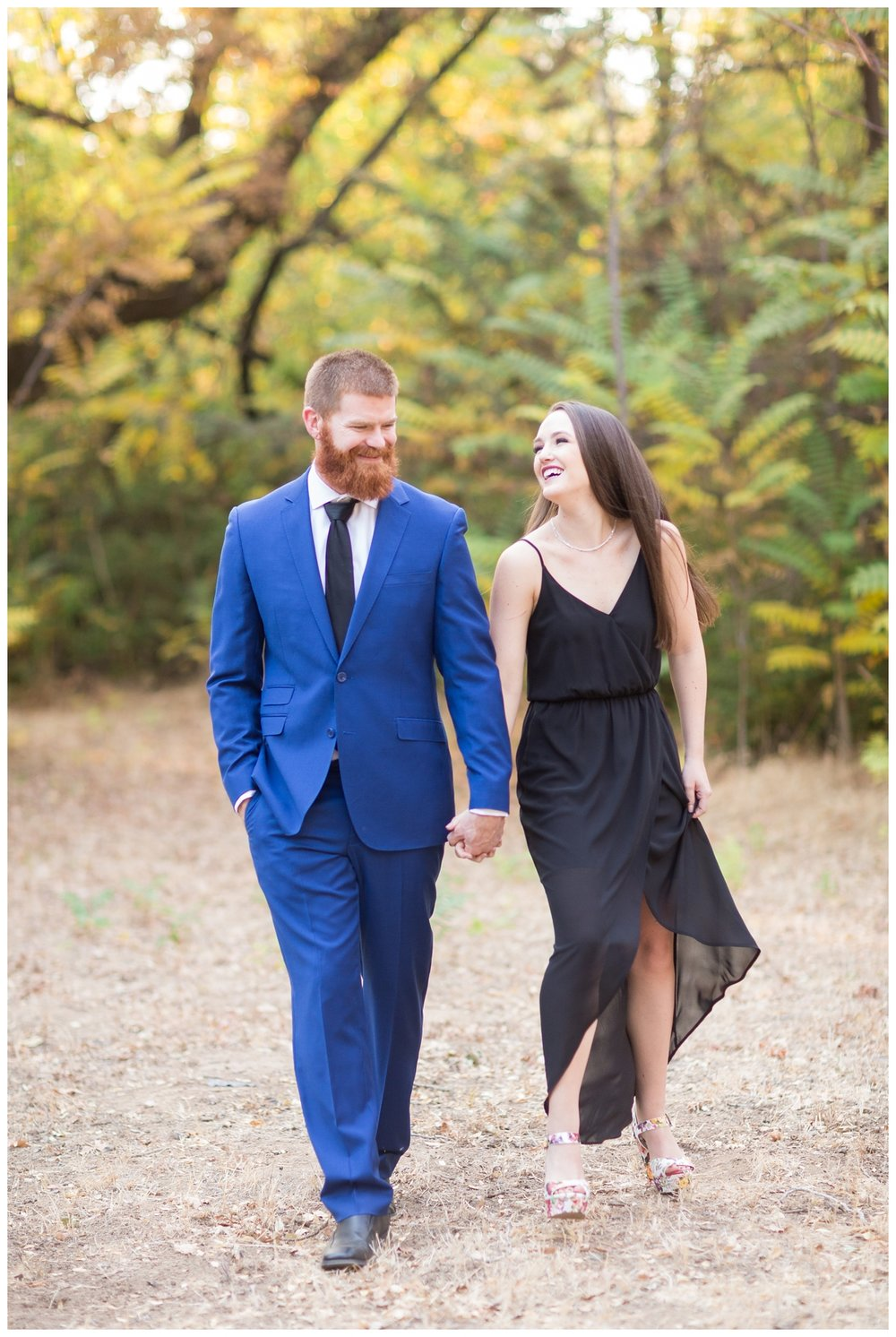engaged couple laughs and walks together while they take photos together in the Tree Farm in Chico California