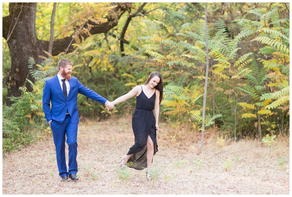 engaged couple walks hand in hand together while they have their phtoos taken