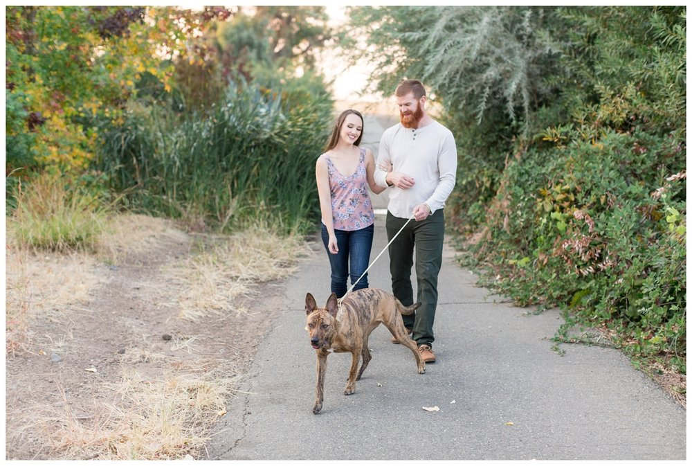 engaged couple takes photos with their dog at a Park in Chico California near the Sacramento River