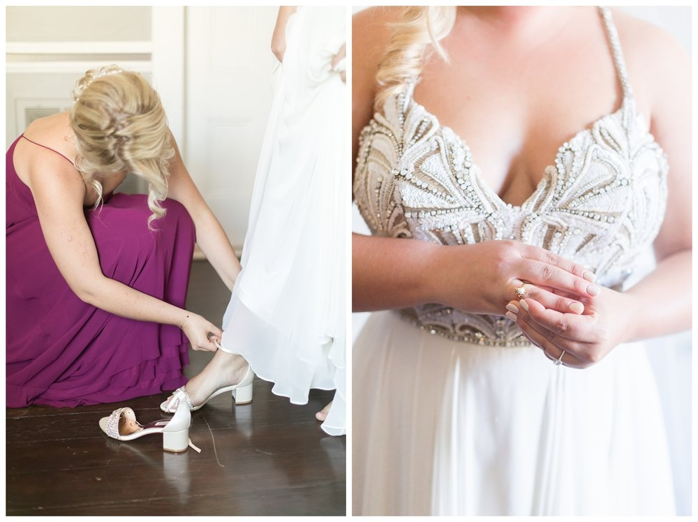 bride having help putting on her wedding dress