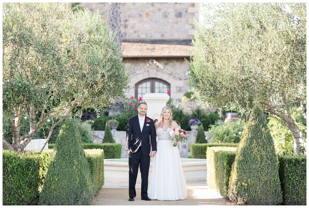 bride and groom walking together while they take photos by a V. Sattui Winery wedding photographer who is located in Napa Wine Country