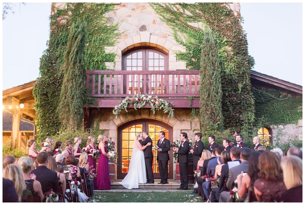 bride and groom exchange rings at V. Sattui Winery at their destination wedding venue in Napa Valley