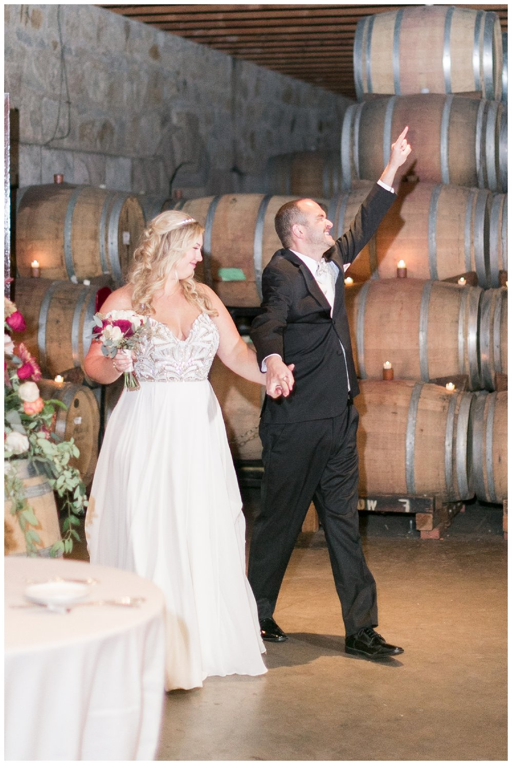 bride and groom enter their indoor wedding reception inside the barrel room at V. Sattui Winery wedding venue in Napa Valley