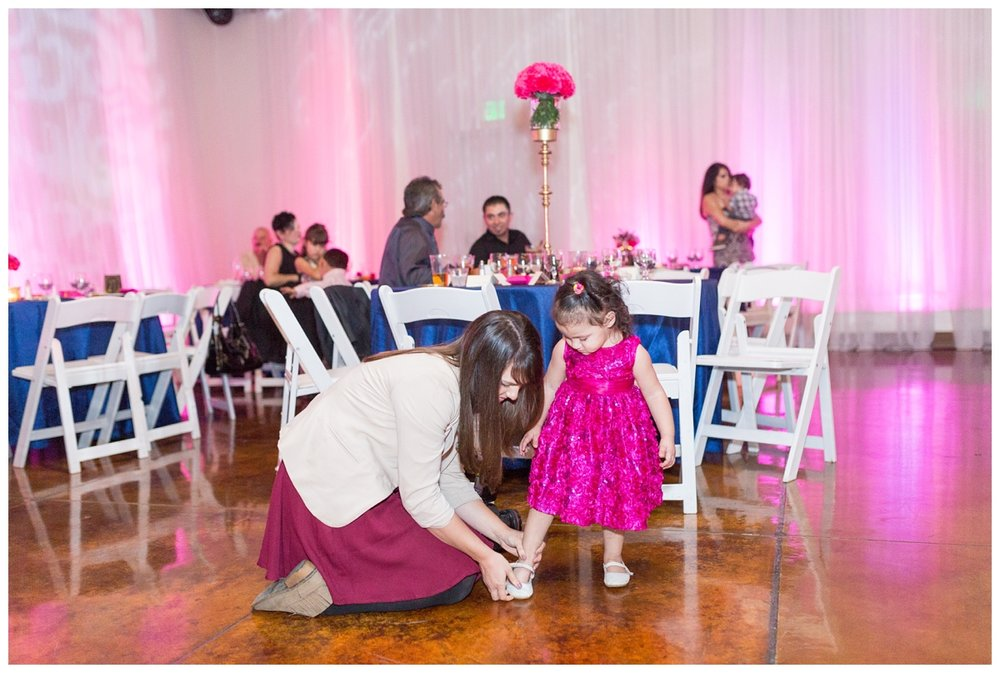 wedding photographer helps a little flower girl put on her shoes