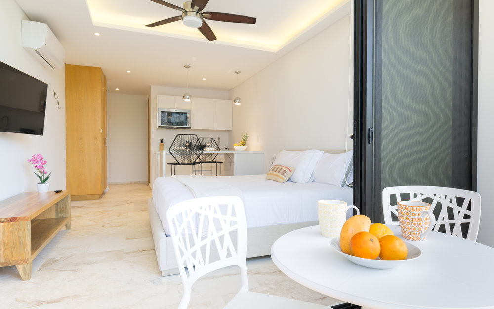 A studio with a king bed, private terrace, bathroom, fully-equipped kitchen, use of common roof deck and infinity pool.