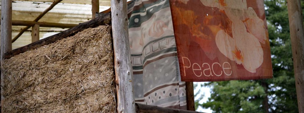 a peace banner hangs from an outdoor structure at Emerald Earth