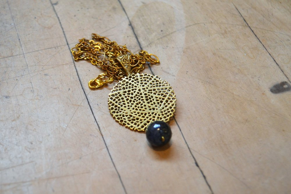 Skeletal Disc Pendant  Contemporary Collection #50, brass with resin drop  $100.00