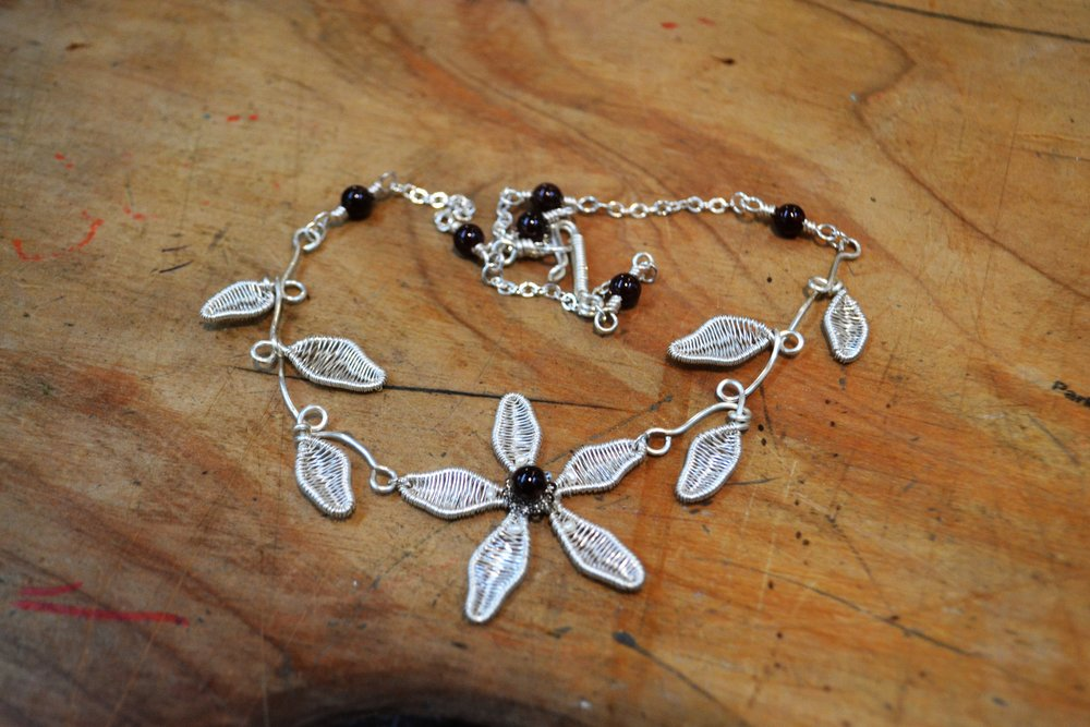AC319  Hand wired flowers and leaves in silver plated artistic wire with Garnets. Stirling silver plated chain. Nickel free.   $190.00