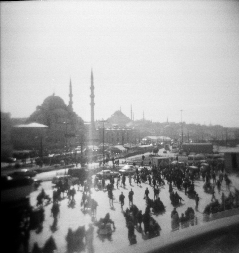 Istanbul On A Holga ( KosmoFoto)  With the Holga, I can catch images that my other cameras wouldn't – a gypsy guitarist at a nighttime festival, the blur of a bird streaking across the city's famous skyline, the doubling of Istanbul faces with Istanbul buildings.