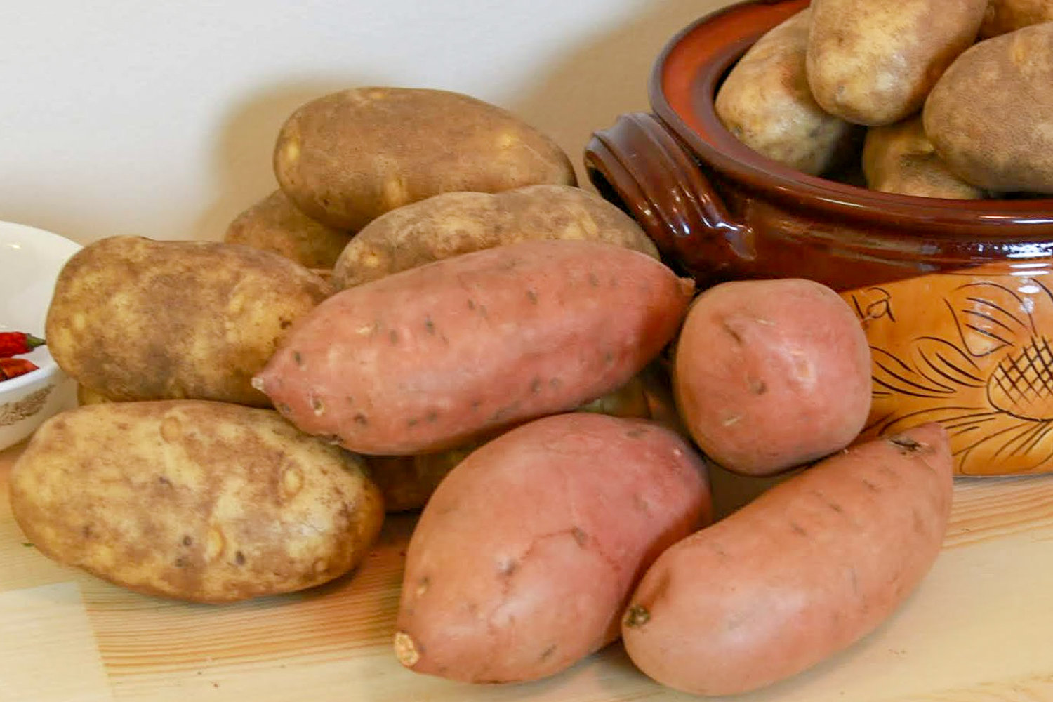 An overflowing container of russet potatoes and sweet potatoes, destined for a baked potato party.