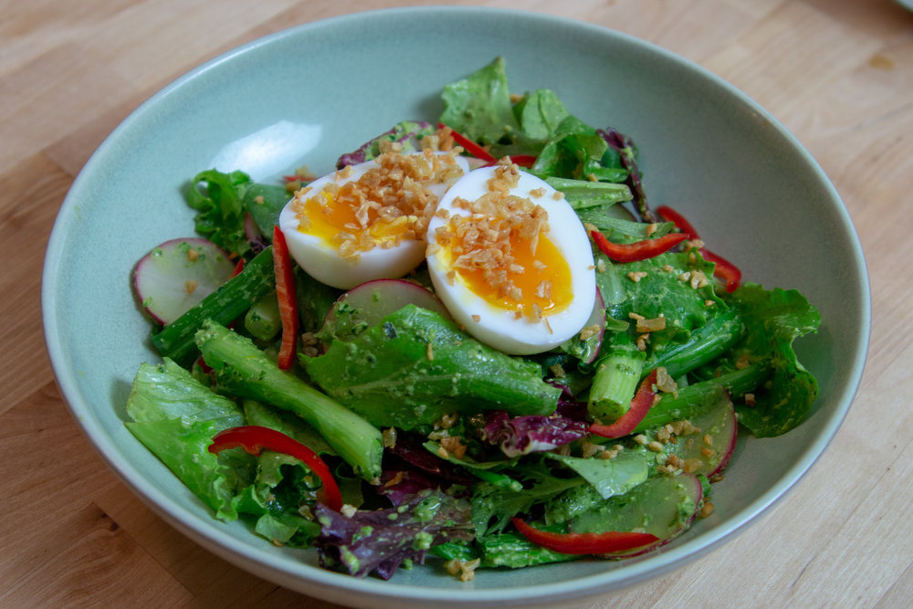 A warm snap pea salad with spinach walnut pesto and a 7 minute egg