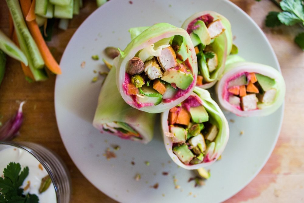 Springrolls made out of cabbage leafs with tofu, beet root hummus and yoghurt lemon dressing