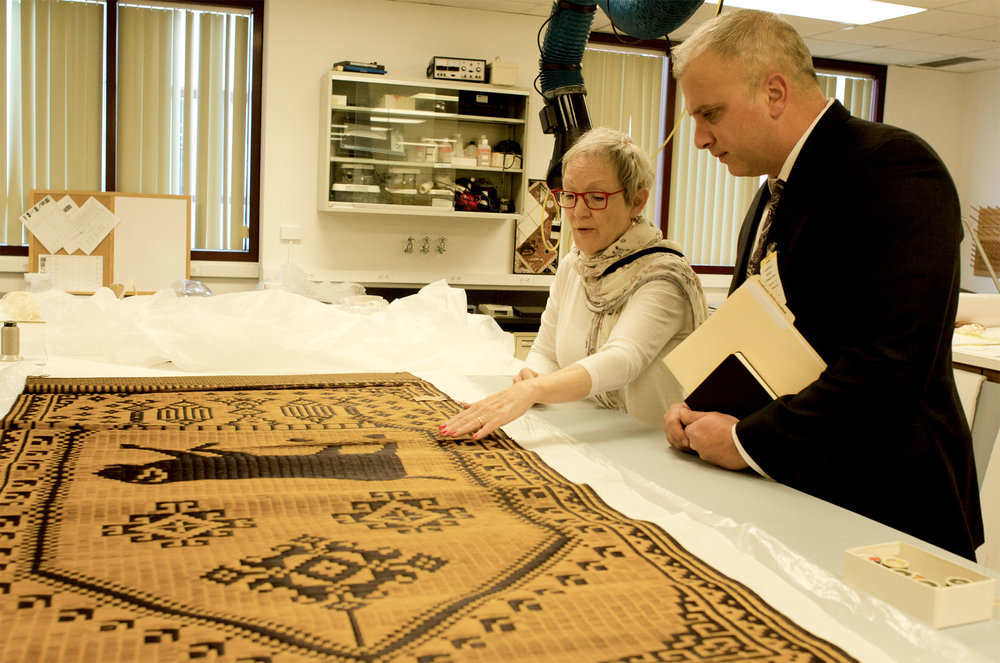 11/30/17 - Smithsonian Institute Museum Support Center Conservation Meeting, Suitland, MD: Object Conservator Kim Cullen Cobb discusses the treatment plan for the woven mat with astrological sign of the dog with Meridian's Vice President of Cultural Programs, Terry Harvey. This meeting is in the conservation lab, and this mat will undergo the most treatment in comparison to the other GGF objects.