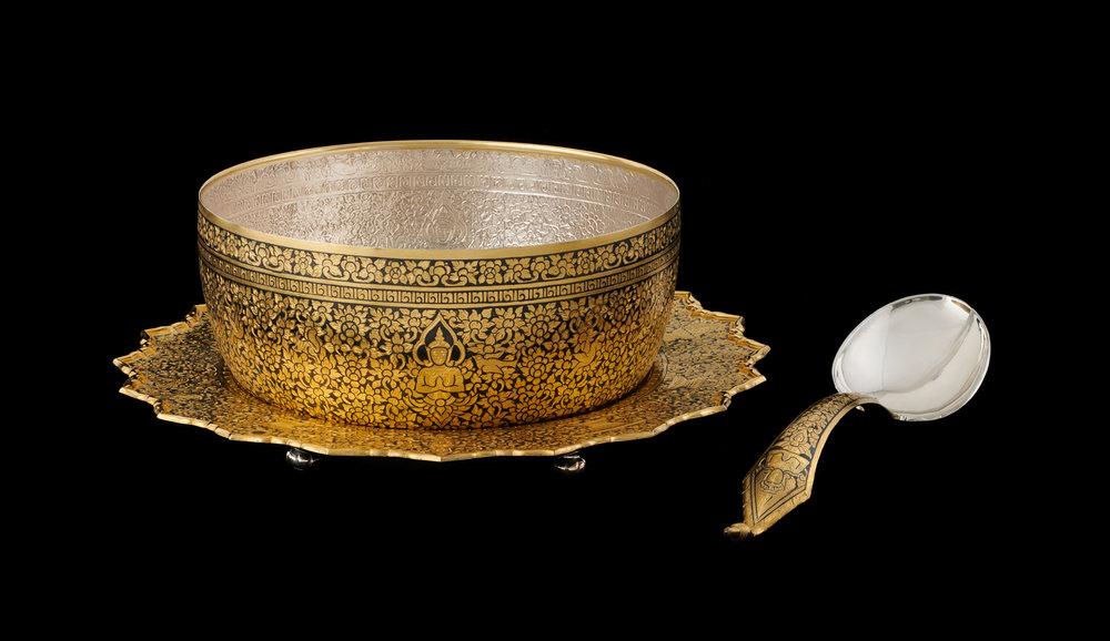 Gold Niello Bowl, Tray, and Ladle Gift from Their Majesties to President Richard M. Nixon and First Lady Pat Nixon, 1969 Bowl: 12.9 x 26 cm; Tray: 36.1 cm diameter; Ladle: 34.3 x 8.8 cm Courtesy of the Richard Nixon Presidential Library and Museum; HS 1969.44.1-3  ขันตักบาตร ถาด และทัพพีถมทอง ของขวัญพระราชทานจากพระบาทสมเด็จพระปรมินทรมหาภูมิพลอดุลยเดชและสมเด็จพระนางเจ้าสิริกิติ์ พระบรมราชินีนาถ แก่ประธานาธิบดีริชาร์ด เอ็ม. นิกสัน และนางแพต นิกสัน สุภาพสตรีหมายเลขหนึ่ง พ.ศ. ๒๕๑๒ ขัน: ๑๒.๙ X ๒๖ ซม. พาน: เส้นผ่านศูนย์กลาง ๓๖.๑ ซม. ทัพพี: ๓๔.๓ x ๘.๘ ซม. ได้รับความอนุเคราะห์จากพิพิธภัณฑ์และหอสมุดประธานาธิบดีริชาร์ด นิกสัน; HS 1969.44.1-3