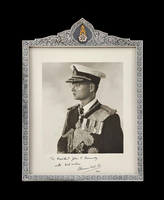 Portrait of King Bhumibol Adulyadej of Thailand in a Silver Niello Frame with Gold Royal Cypher Gift from King Bhumibol Adulyadej to President John F. Kennedy, 1963 38.1 x 26 cm Courtesy of the John F. Kennedy Presidential Library and Museum; MO 76.307  พระบรมฉายาลักษณ์พระบาทสมเด็จพระปรมินทรมหาภูมิพลอดุลยเดชแห่งราชอาณาจักรไทย ในกรอบถมเงินประดับอักษรพระปรมาภิไธย ภ.ป.ร. ภายใต้พระมหาพิชัยมงกุฎ ของขวัญพระราชทานจากพระบาทสมเด็จพระปรมินทรมหาภูมิพลอดุลยเดช แก่ประธานาธิบดีจอห์น เอฟ. เคนเนดี พ.ศ. ๒๕๐๖ ขนาด ๓๘.๑ x ๒๖ ซม. ได้รับความอนุเคราะห์จากพิพิธภัณฑ์และหอสมุดประธานาธิบดีจอห์น เอฟ. เคนเนดี; MO 76.307