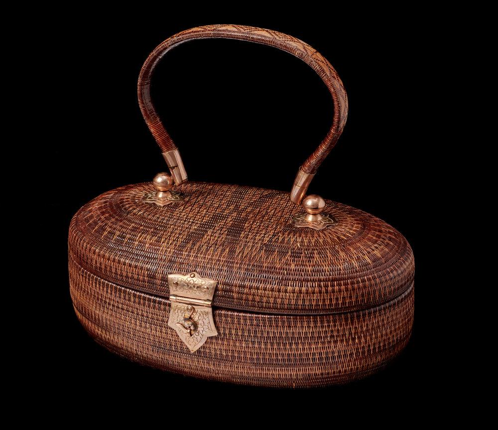 SUPPORT Foundation Yan Lipao Vine Woven Purse Gift from Queen Sirikit to First Lady Rosalynn Carter, 1979 10.2 x 20.2 x 12.7 cm Courtesy of the Jimmy Carter Presidential Library and Museum; 79.10.1  กระเป๋าย่านลิเภาจากมูลนิธิส่งเสริมศิลปาชีพฯ ของขวัญพระราชทานจากสมเด็จพระนางเจ้าสิริกิติ์ พระบรมราชินีนาถ แก่นางโรซาลินน์ คาร์เตอร์ สุภาพสตรีหมายเลขหนึ่ง พ.ศ. ๒๕๒๒ ๑๐.๒ x ๒๐.๒ x ๑๒.๗ ซม. ได้รับความอนุเคราะห์จากพิพิธภัณฑ์และหอสมุดประธานาธิบดีจิมมี คาร์เตอร์; 79.10.1