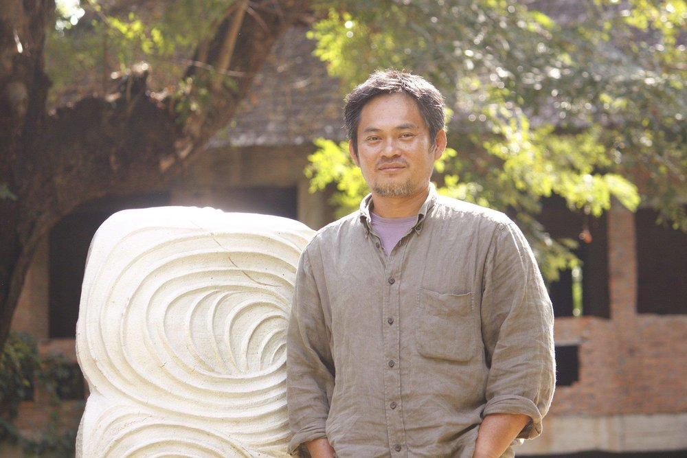 Amornthep is a true artist, a potter's potter in his mastery of techniques – he devotes two months each year to teaching young ceramic students; and an individual thinker, painstakingly progressing along his very own and hidden lines. Steeped into the Japanese tradition, he wholly immersed himself into his work, most of which is then fired in one of the wood kilns that he has built at Sen Moo, his studio hidden in the hills of Mae Taeng.  Far from the agitation of Chiang Mai, on the edge of this small village, Amornthep spends his days steadily building a world all of his own. It is a very introspective work but also whimsical; sometimes poetic, sometimes funny, sometimes childish and at other times deeply serious. The words that recur in my mind writing this are meditative and poetic substance.   A lot of his work is inspired by raw nature and always somehow water, still or running, is the perfect foil for his work. Sweet shapes of natures, wispy grasses, flowers, rice they have all found their way into his pieces. Experimenting with material to create new textures and colours on the finished forms. For a long time most of the colours came from the clay or the fire, very natural earthy tones with black and red hues. More recently colours are making a comeback in his work, more vivid and shiny and impetuous.  His larger pieces actually often consist of myriads of smaller shapes that are painstakingly assembled to create larger sculptures. Many of these actually curl up on themselves suggesting an inner world, or rather beautiful barricades protecting an inner sanctum.  Some of the heavier forms that he creates are adorned with lines some like short and curled arabesques, and others long and recurrent spinning onto themselves like the white cotton threads in a Buddhist blessing. There are also the mysterious boats heavy fortresses of clay adorned with patches of colour and engraved with sybiline scriptures..  And then the sweet and naïve animal forms he uses to decorate the more humble tea pots and jars for domestic use, all embued with a delicate yet functional beauty.  It is difficult to summarise Amornthep's work. A comprehensive knowledge of clay and firing techniques, a deep interest in print making combined with two decades of experience mean that he can apply his talent to many things from a humble chawan to a three dimensional kinetic sculpture.