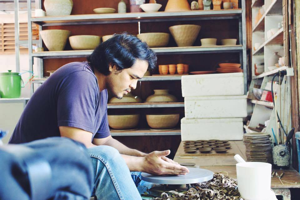 thai artist working on pottery.jpg