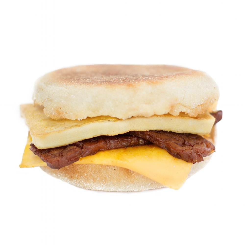 Bacun maple crunch (GF) - Our delicious breakfast sandwiches include one hand cut tofu egg seasoned with black salt for an eggy flavour without any egg.  We pair it with a slice of American style cheddar cheese and serve it on a toasted white or whole wheat english muffin.   Add your choice of vegan ham, house made bacUN or vegan sausage!