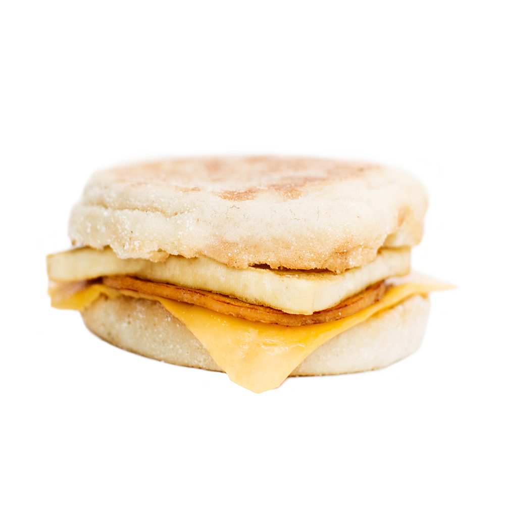 Breakfast Sandwich with Ham - Our delicious breakfast sandwiches include one hand cut tofu egg seasoned with black salt for an eggy flavour without any egg. We pair it with a slice of American style cheddar cheese and serve it on a toasted white or whole wheat english muffin.  Add your choice of vegan ham, house made bacUN or vegan sausage!