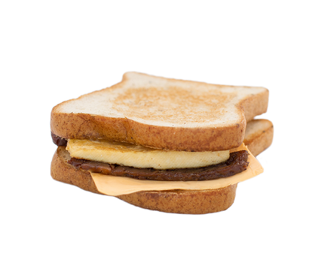 bacun breakfast sandwich (gf) - Our delicious breakfast sandwiches include one hand cut tofu egg seasoned with black salt for an eggy flavour without any egg.  We pair it with a slice of American style cheddar cheese and serve it on a toasted white or whole wheat english muffin.