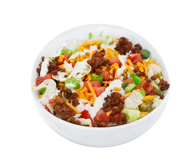 bacun taco salad (GF) - Enjoy this gluten-friendly salad that has bacUn bits as an alternative to taco meat without compromising on flavour!  It starts with crispy iceberg lettuce, then is topped with fresh sour 'cream'.  We then add grilled smokey bacUn bit, diced tomatoes, green onions and cheddar style shreds.