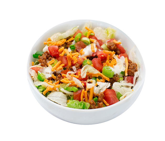 taco salad - This fresh salad starts with crispy iceberg lettuce and is topped with our fresh sour 'cream'.  We then add vegan taco meat, diced tomatoes, green onions and cheddar style shreds.