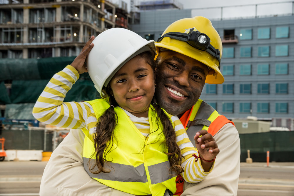 Construction worker hugging his young daughter.