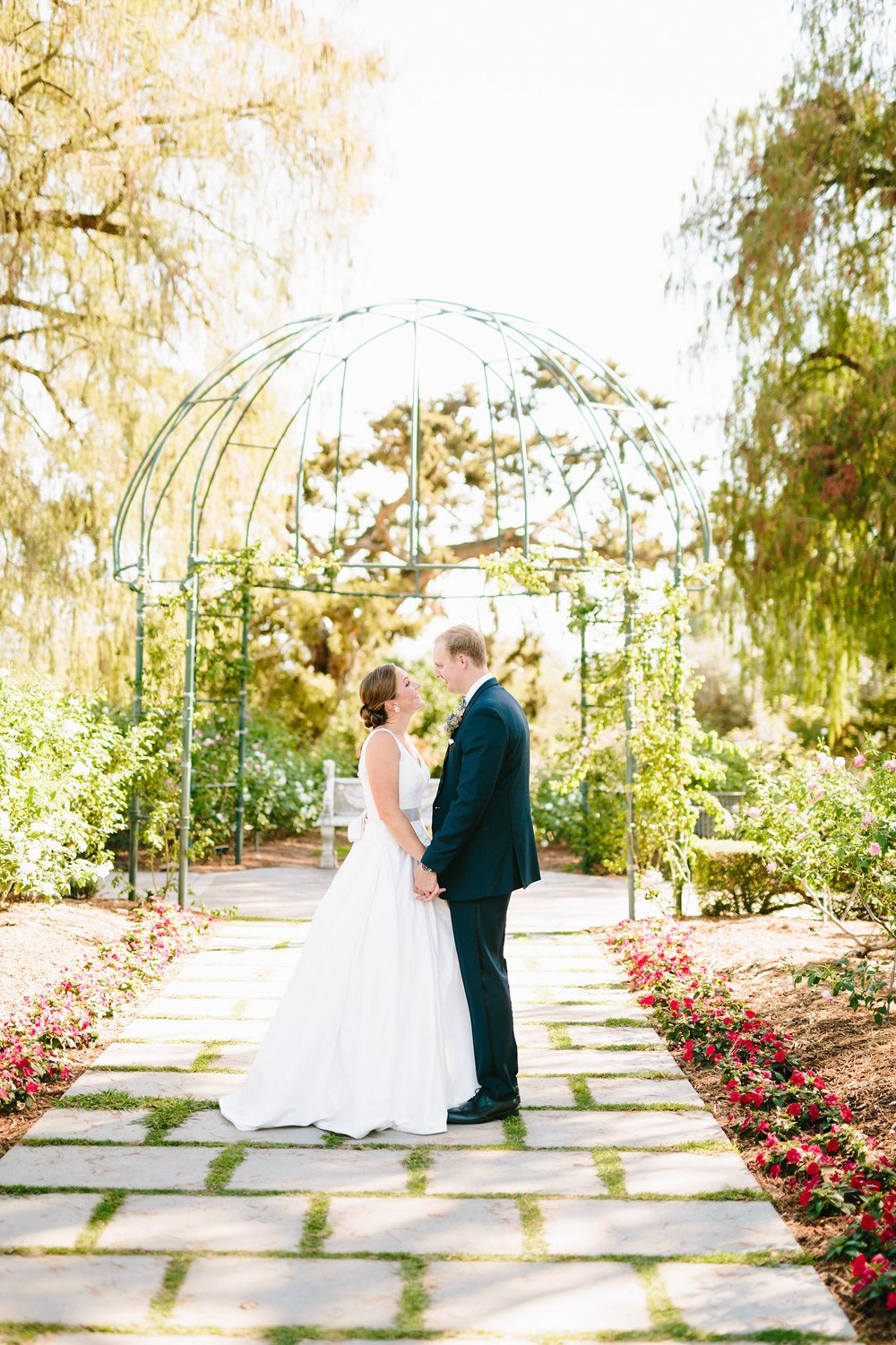 Bride and groom on a path in the Rose Garden at the Huntington Library and Gardens.