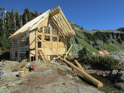 The roof trusses are nearly all in place. The large yellow cedar columns were donated by partnering First Nations, and will stand in front. The left hand one is already in place.