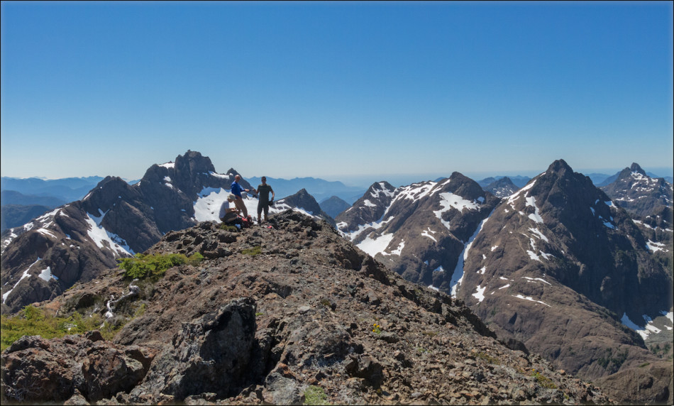 Left to right: Kevin, Mike, and Chris on top of Thumb Peak. Mt. Bate is in the background directly behind the lads, Little Alava to the right, and Mt. Alava proper to the right of the long snow gully. Photo by Mary Sanseverino.