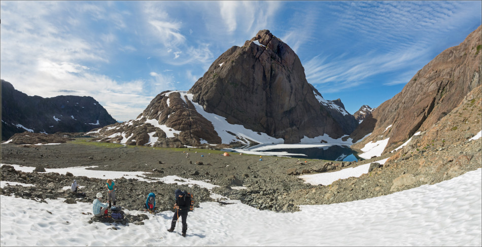 Getting ready to head up the snowfield in the couloir north of camp. In the image, left to right: Gail, Rita (in plaid shirt), Liz, Vincent (putting on gaiters), and Neil (checking his ice axe). The northern buttress of Mt. Bate rises over our camp on the lake. Photo by Mary Sanseverino.