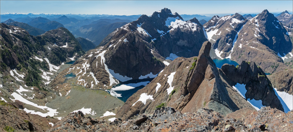 On Thumb Peak looking across the au cheval ridge at the gendarme known as The Thumb. The camp on Shangri-La Lake and The Spa are in the basin on the left. Mt. Bate is the peak directly to the left and above The Thumb. To the right are Little Alava Peak and Mt. Alava with Peter Lake below. The Pacific Ocean is off on the right horizon, and the mountains of Strathcona Provincial Park rise on the left horizon. Photo by Mary Sanseverino.