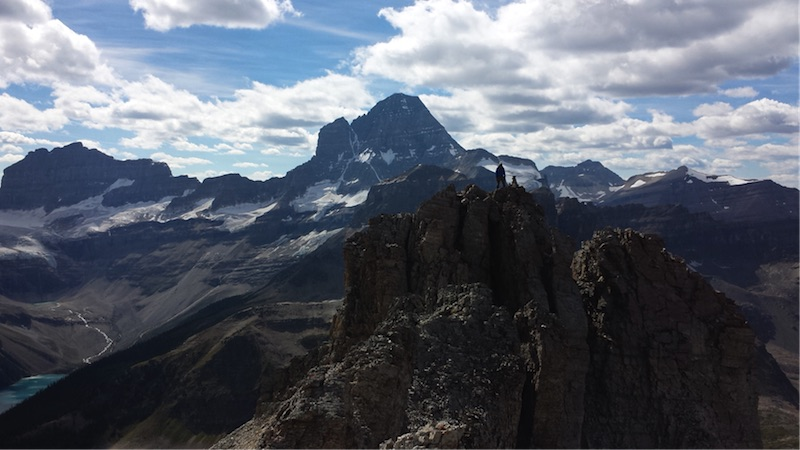Kirk Bishop standing on the summit of Wonder Peak – with Lake Gloria and the east face of Mt. Assiniboine. Photo by Susan Courty.