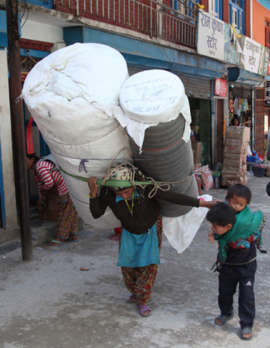 Nepalese woman carrying a crazy load and managing her children at the same time!