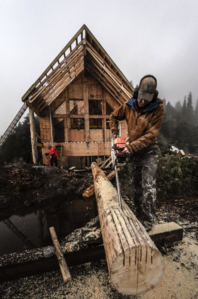 Preparing the Yellow Cedar tree that will be used for the hut's front center post. Thank you to the hereditary chief from the Tla-o-qui-aht First Nation that donated the three trees that form the hut's front posts. Photo by Chris George.