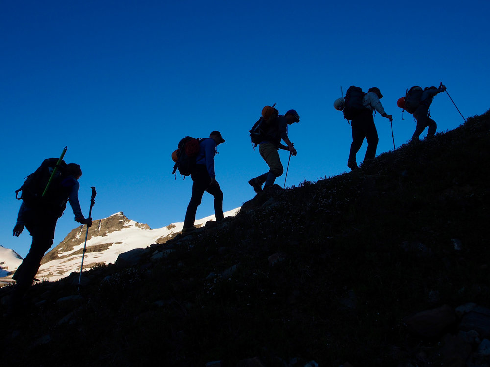"""A group of climbers make their way over the moraines leading to the """"Riddle """" glacier during week 2 at the 2018 GMC. Climbs on this side the valley called for 4am wake-ups and boots on the trail by 5am. Photo: Jeff Stokoe."""