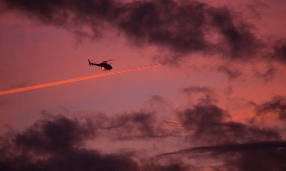 Helicopter and Contrail at Sunrise