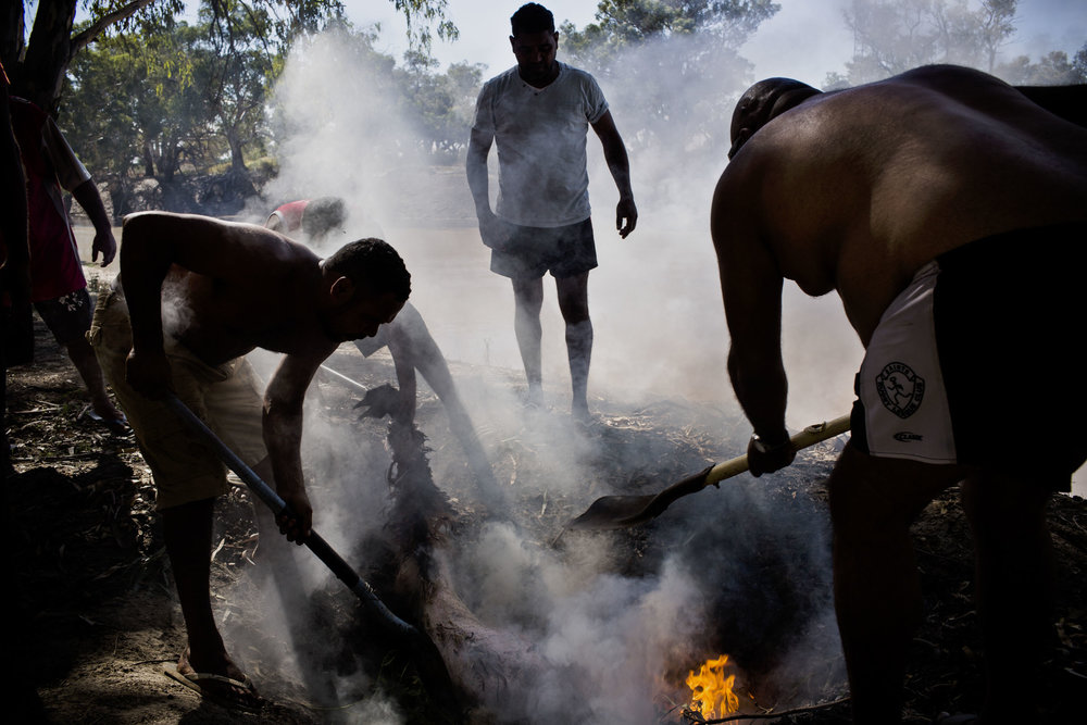 Barkindji men cook a hunted Emu in the ground the traditional way in Wilcannia, NSW.