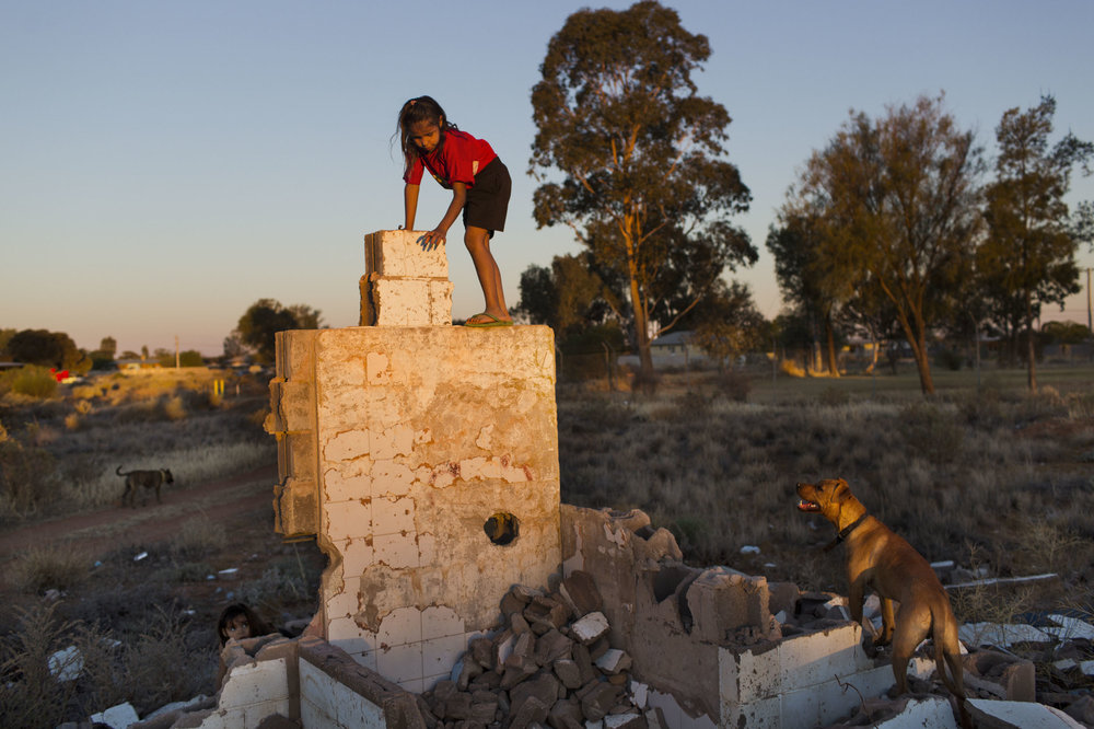 Children play in what remains of an abandoned house in Wilcannia, NSW.
