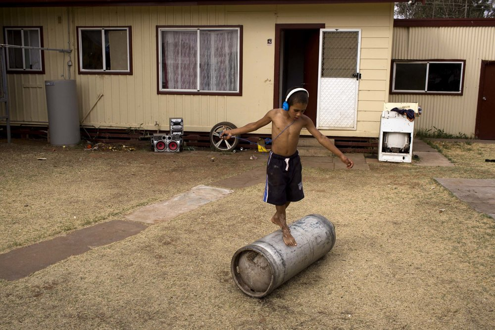 A boy plays in the backyard of a neighbours home in Wilcannia, NSW.